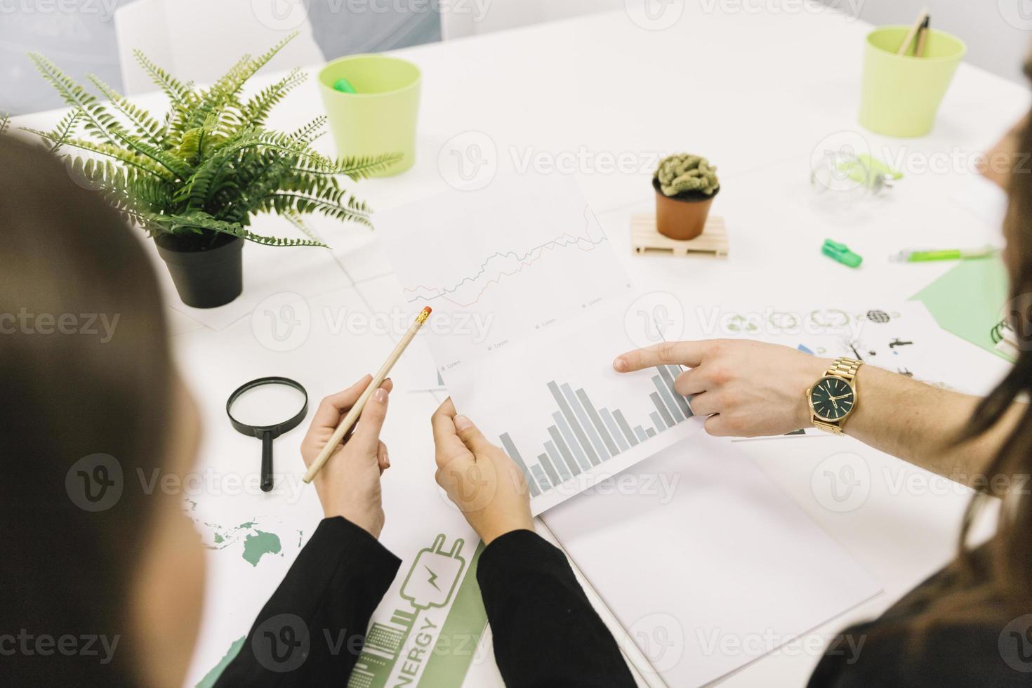 Gruppe von Geschäftsleuten, die Grafik im Büro analysieren foto