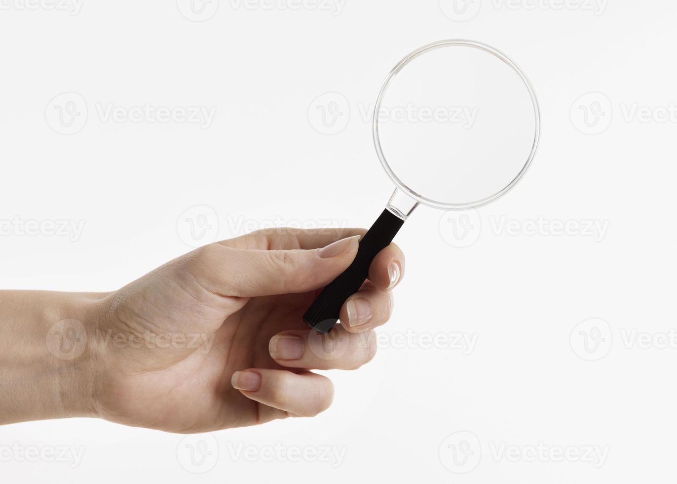 Hand hält eine Lupe auf weißem Hintergrund foto
