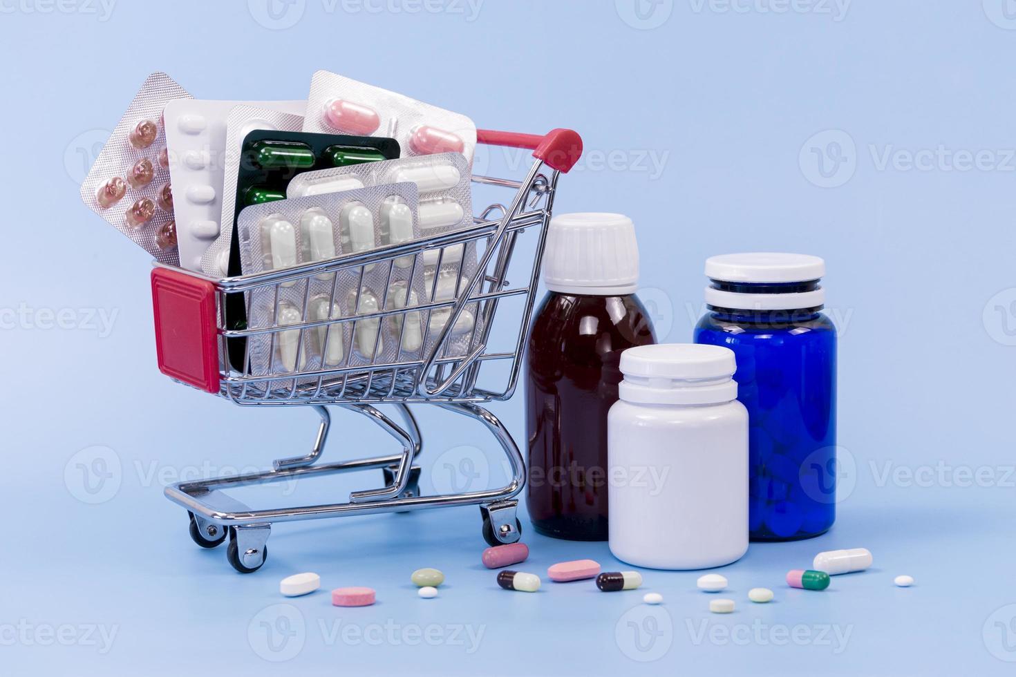 Hochwinkel-Pillenflossenöle und Plastikbehälter mit Miniatur-Einkaufswagen auf blauem Hintergrund foto