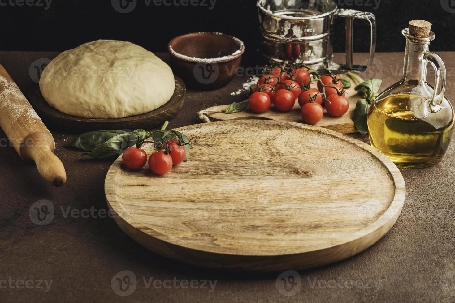 hoher Winkel des Pizzateigs mit Holzbrett und Tomaten foto