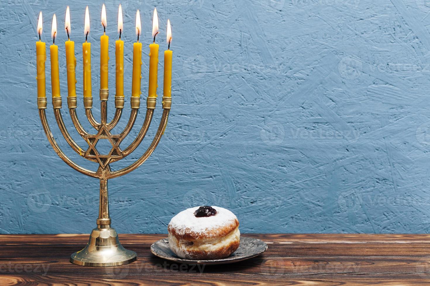 jüdische Menora mit leckerem Donut auf blauem hölzernem Hintergrund foto