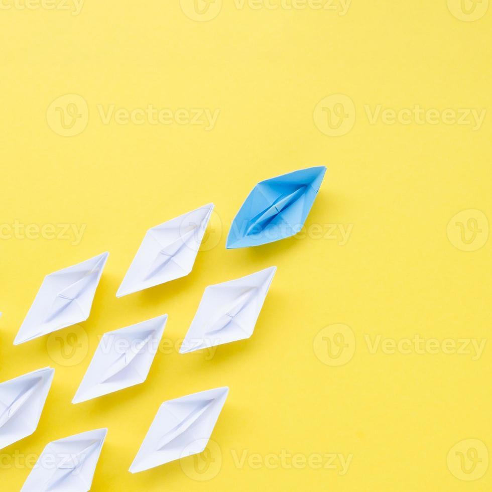Zusammensetzung des Individualitätskonzepts mit Papierbooten auf gelbem Hintergrund foto