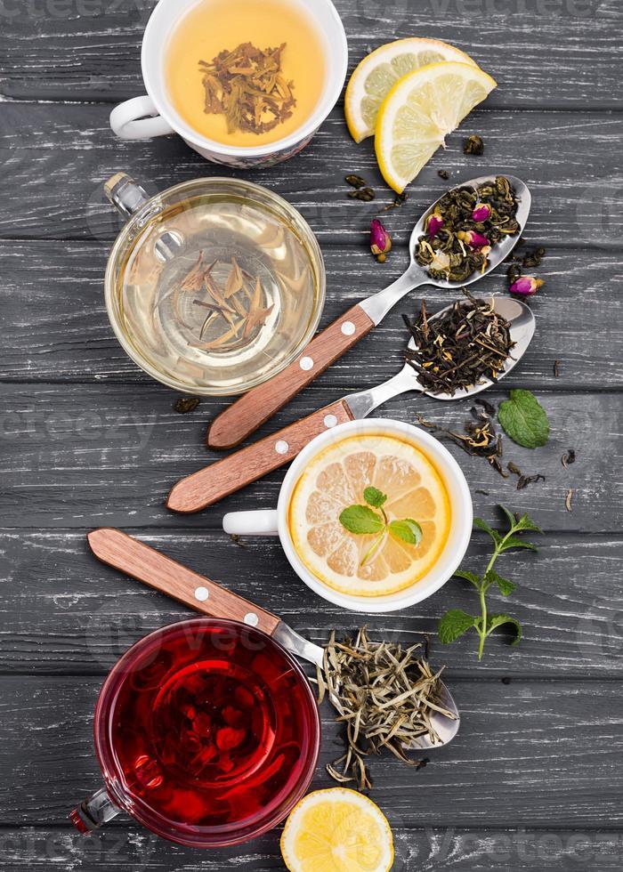 Tasse Tee mit Kräutern auf hölzernem Hintergrund foto