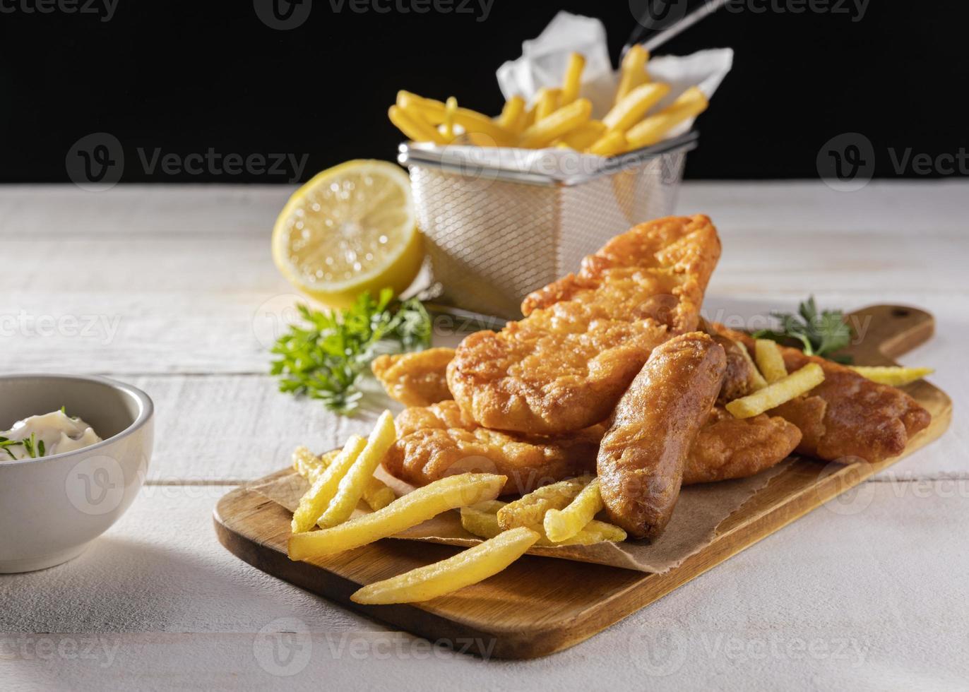 Fish and Chips auf Schneidebrett mit Zitrone foto
