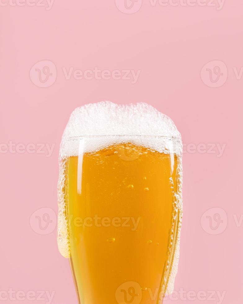 Glas mit Bier und Schaum auf rosa Hintergrund foto
