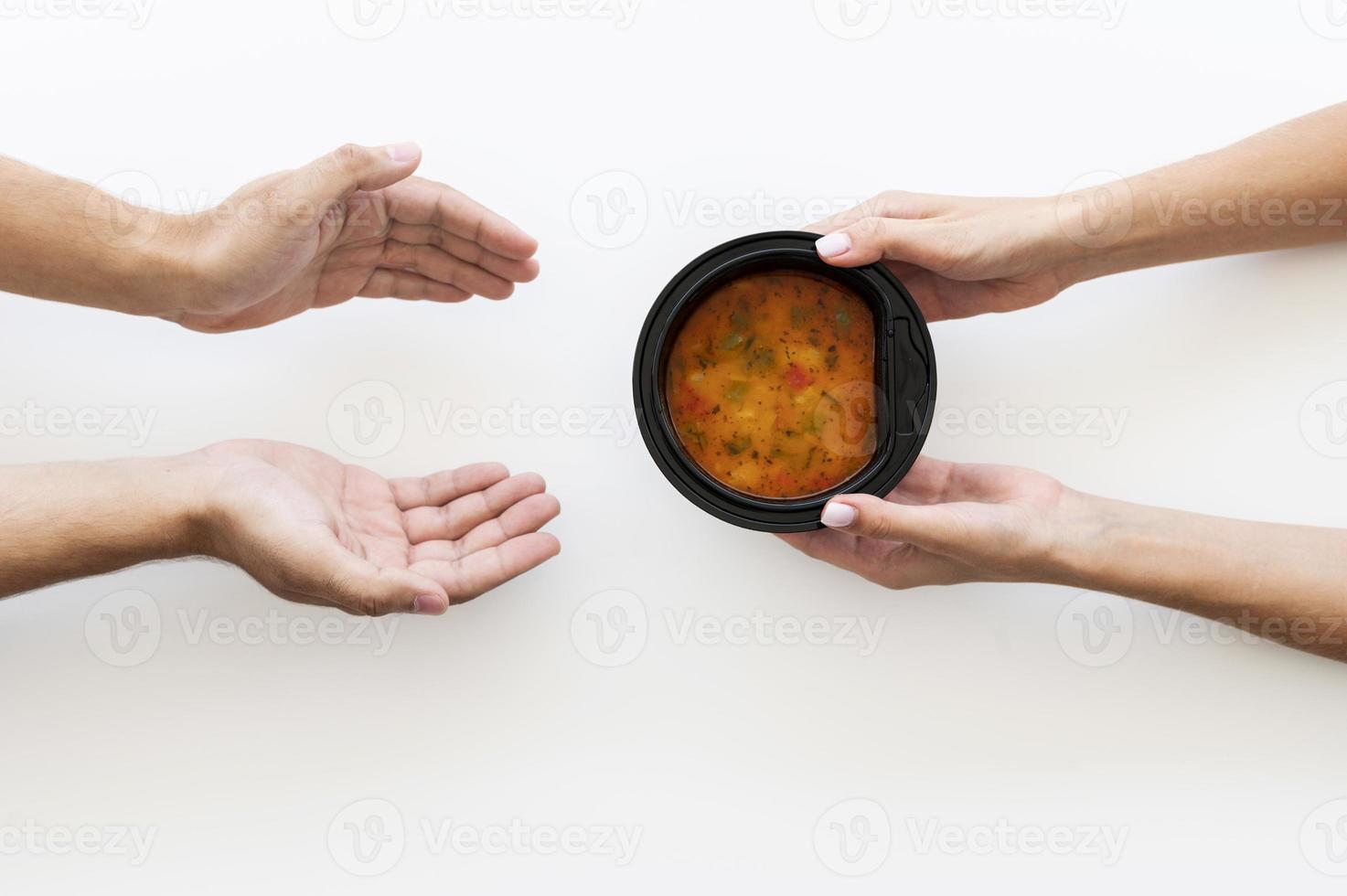 Hand, die einer bedürftigen Person eine Schüssel Suppe gibt foto