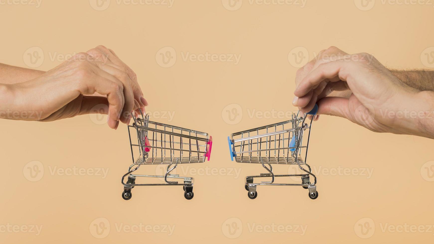 Hände, die kleine Einkaufswagen auf Pfirsichhintergrund halten foto