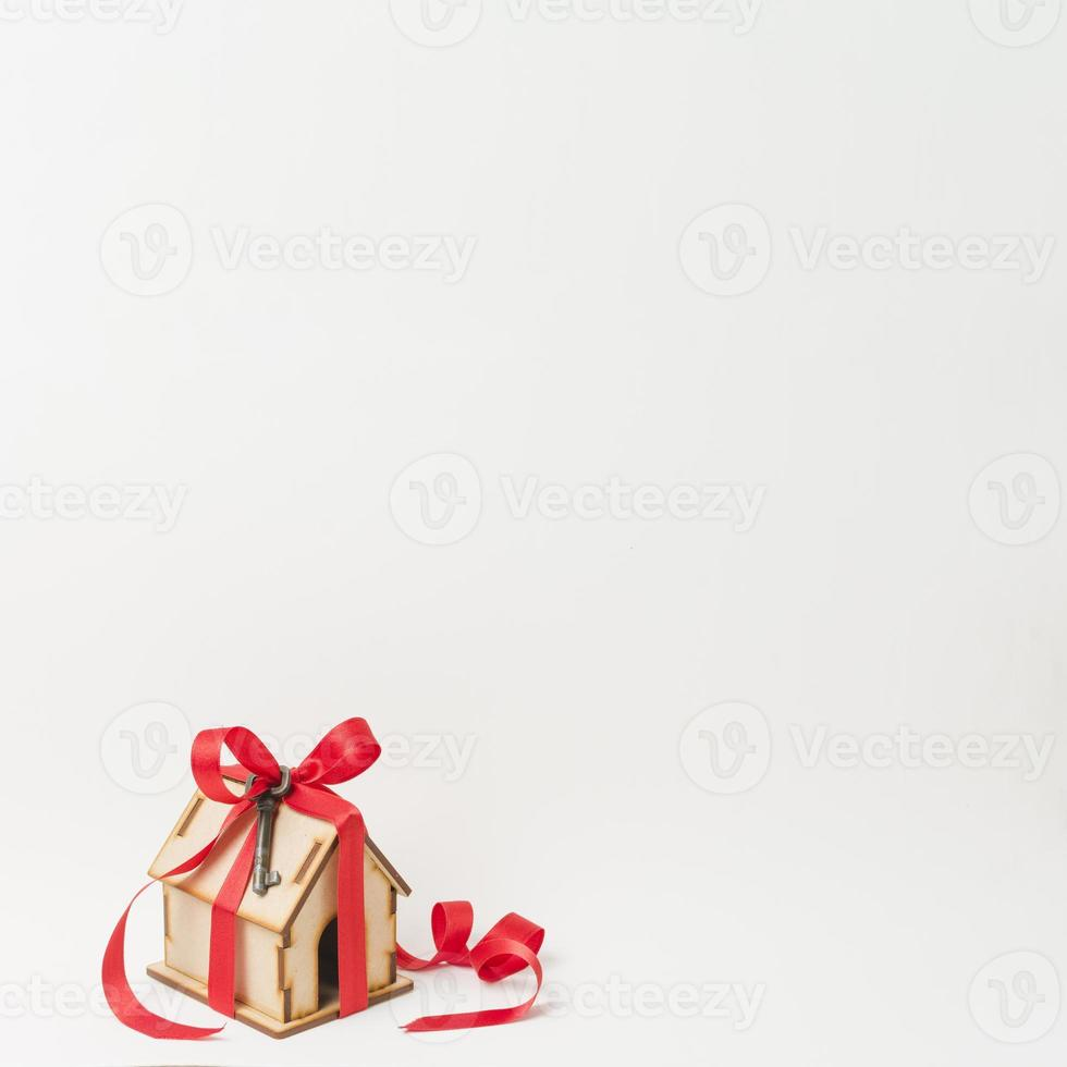 Modellhaus und Metallschlüssel durch rotes Band mit Raumtext auf weißem Hintergrund gebunden foto