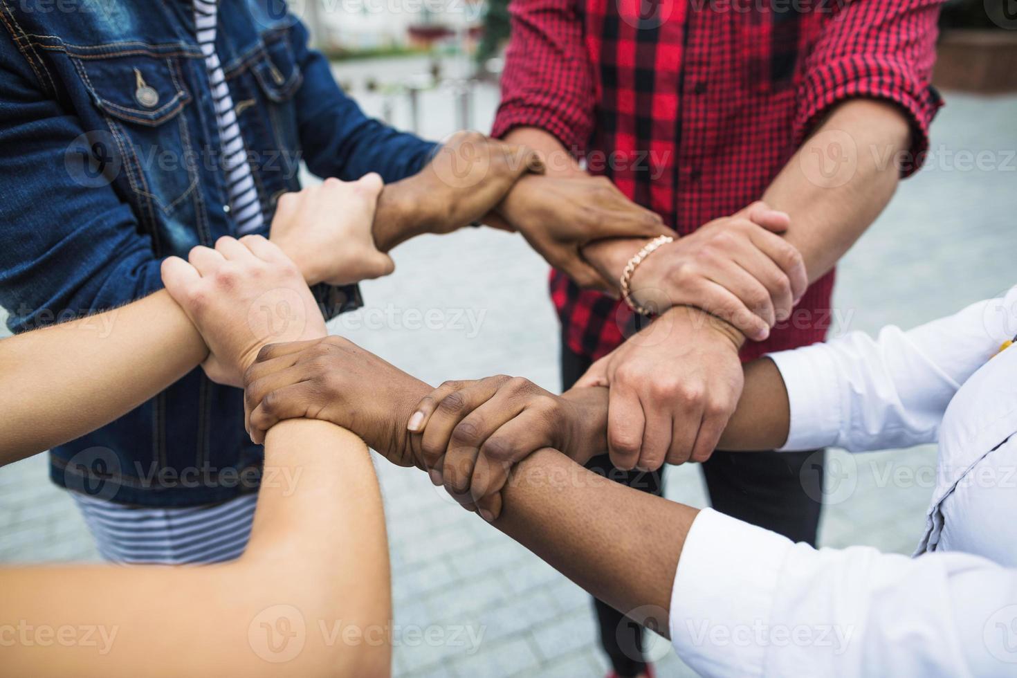 anonyme gemischtrassige Menschen, die Hände stapeln foto