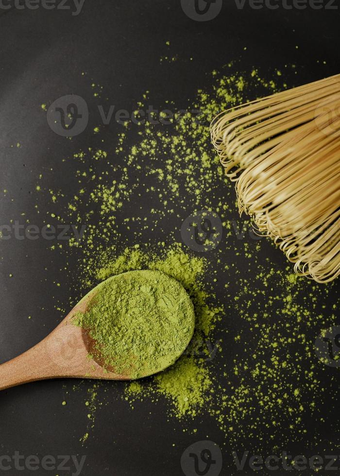 Nahaufnahme Matcha Teepulver auf Holzlöffel mit Bambus Schneebesen foto