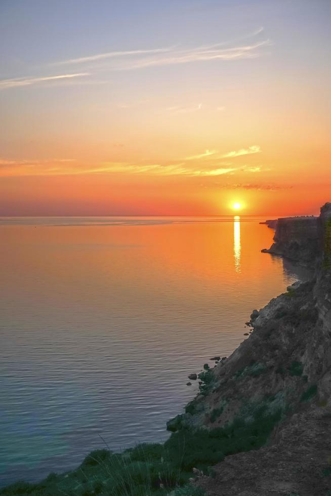 bunter orange Sonnenuntergang über einem Meer und einer felsigen Küste foto