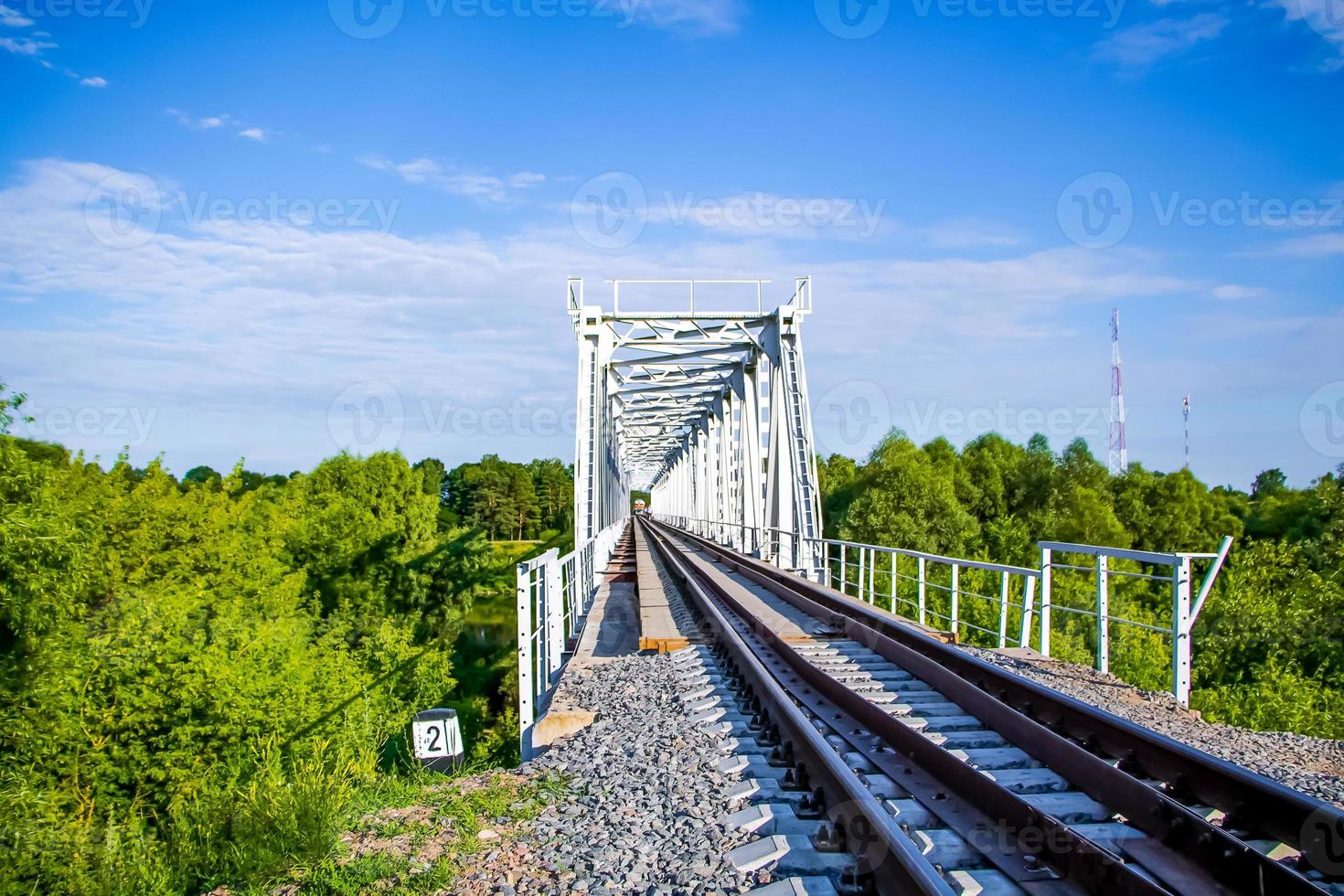 schöne Eisenbahnbrücke auf einem Hintergrund des Grüns und des blauen Himmels, Perspektive foto