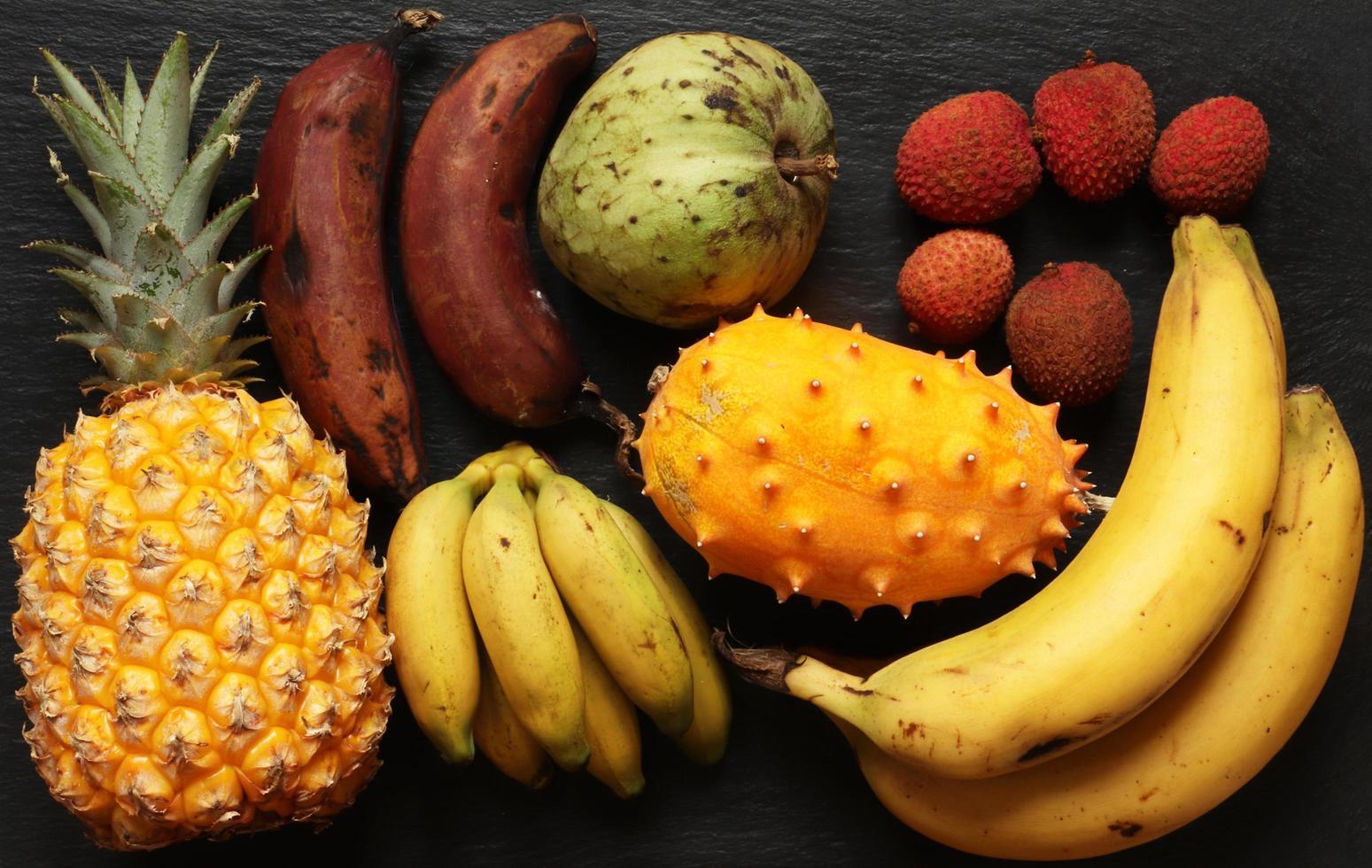 Foto von mehreren tropischen Früchten auf Schieferhintergrund für Lebensmittelillustration