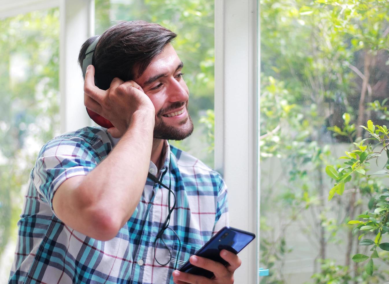 gutaussehender Mann, der glücklich Musik hört foto