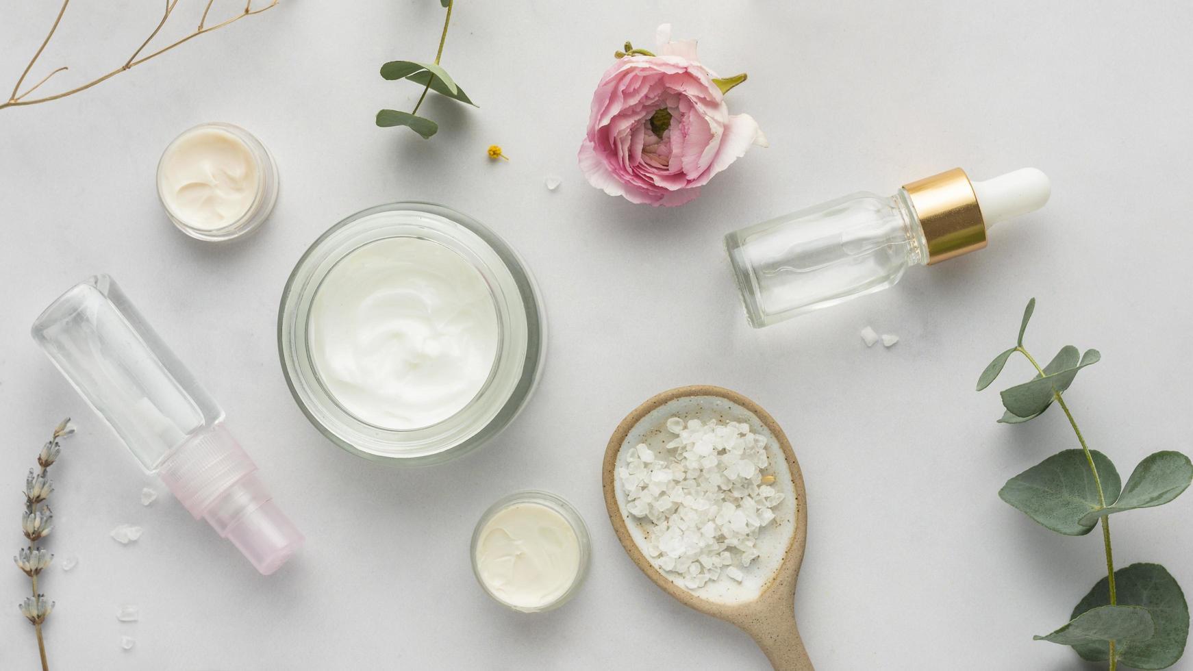 Gesichtscreme und Blumen auf weißem Hintergrund foto