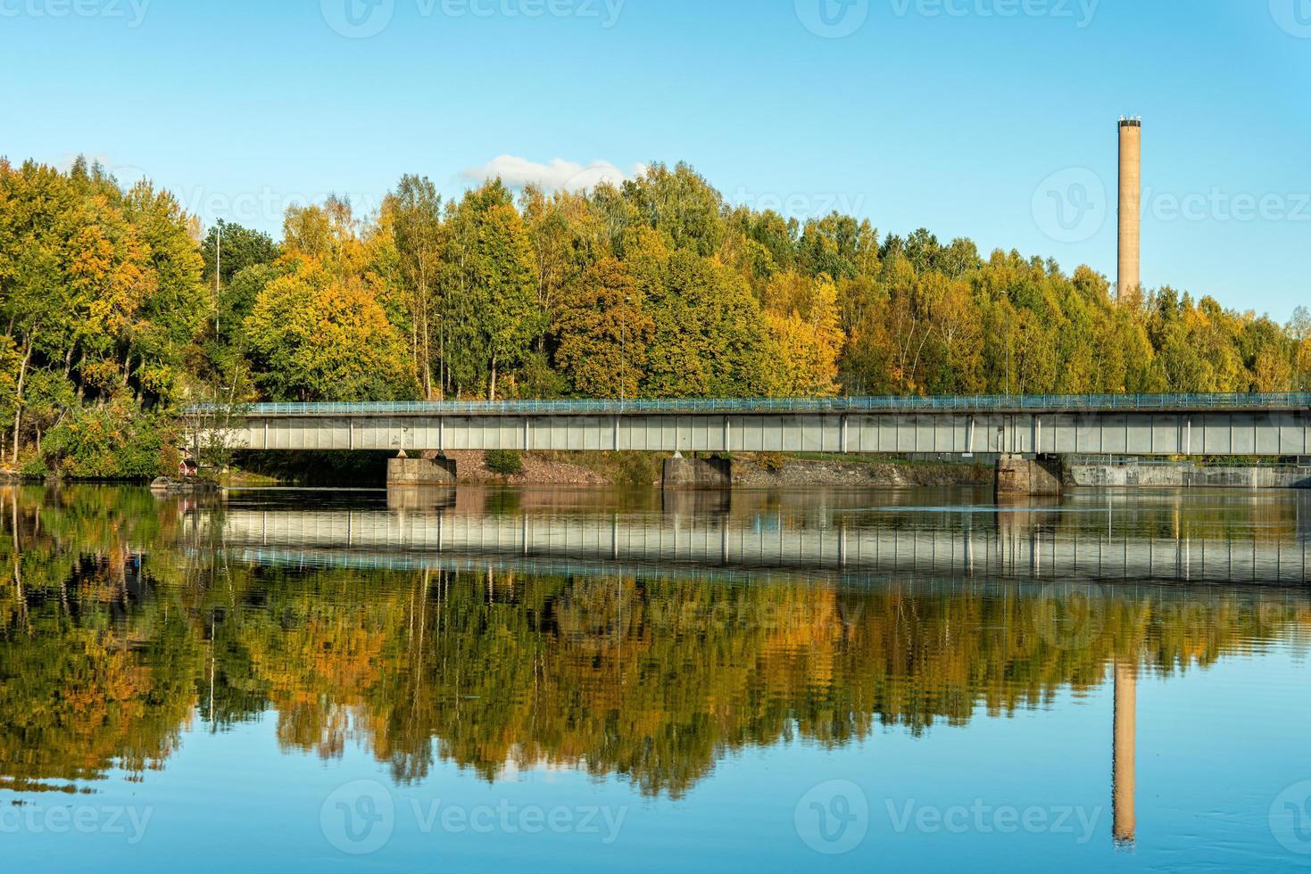 Herbstansicht einer niedrigen Brücke, die einen Fluss in Schweden überquert foto