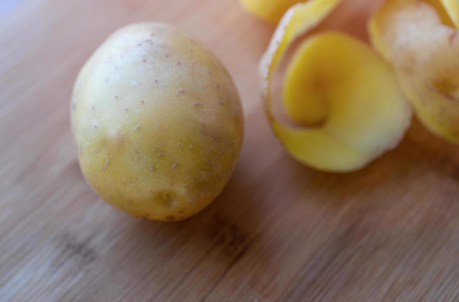 rohe Kartoffeln mit Schale auf einem Schneidebrett foto