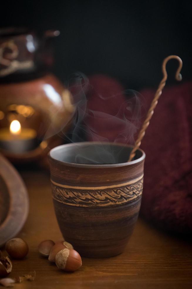 dunkler Hintergrund mit einem heißen Getränk in einer Keramik foto