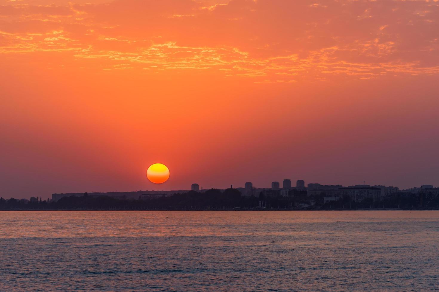heller Sonnenuntergang über einem ruhigen Meer und buntem Himmel foto