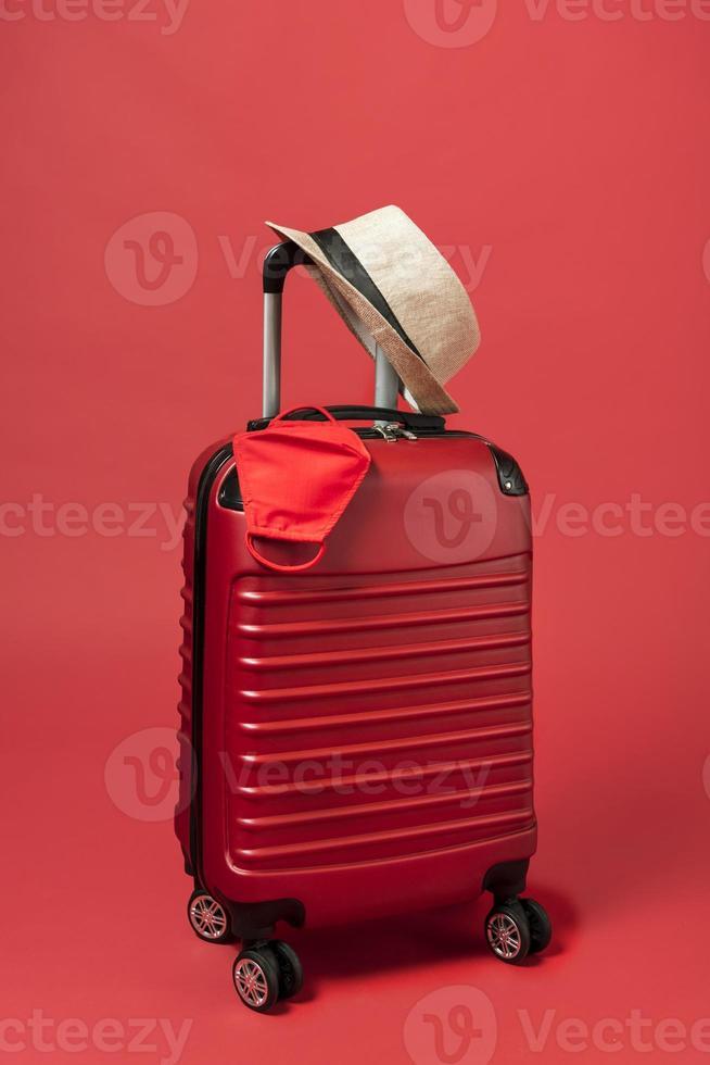 rotes Gepäck mit Hut und Maske auf rotem Hintergrund foto