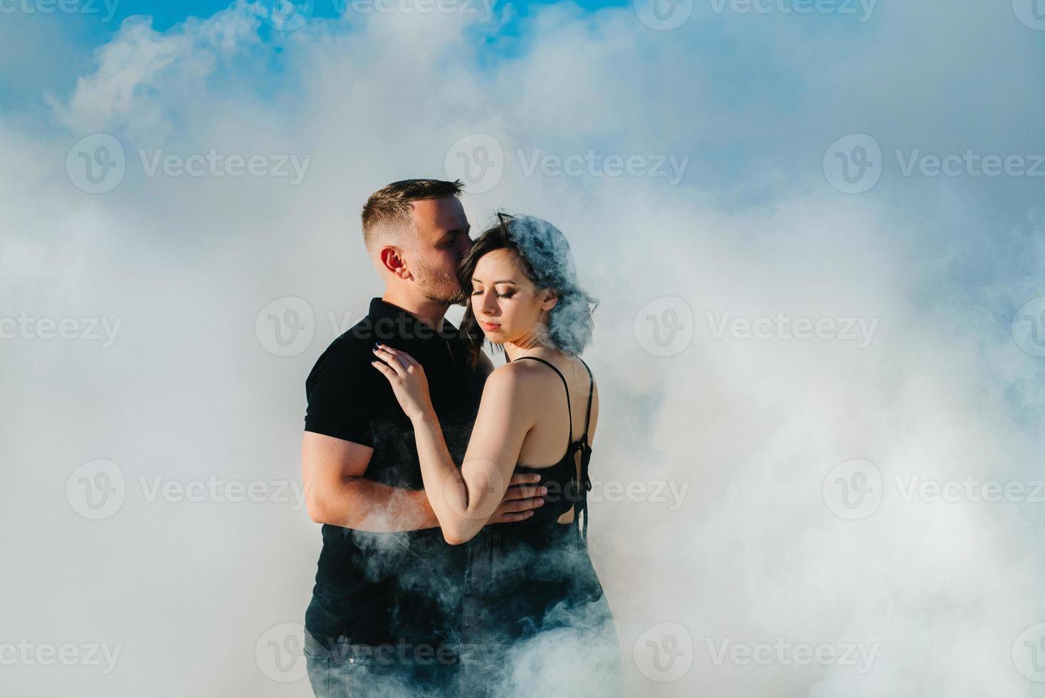 Mann und ein Mädchen in schwarzer Kleidung umarmen sich in weißem Rauch foto