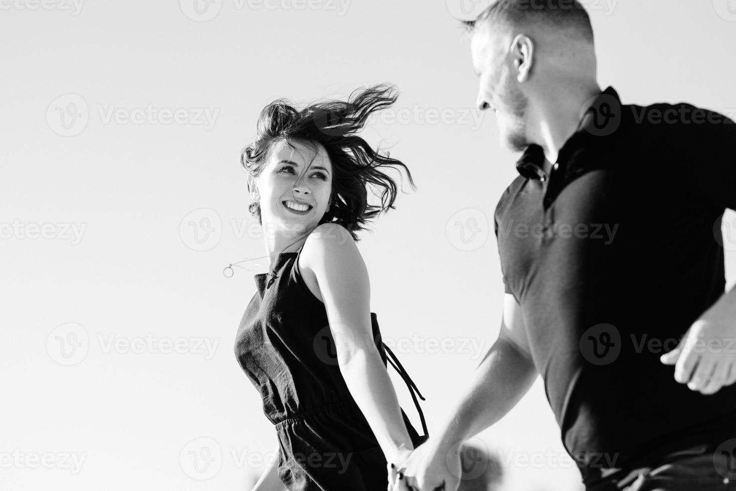 junges Paar ein Mann und ein Mädchen mit freudigen Gefühlen in schwarzen Kleidern gehen durch die weiße Wüste foto