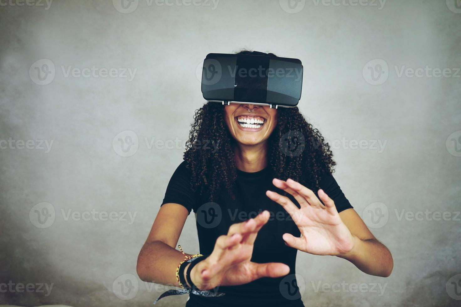 Eine schöne junge schwarze Frau mit lockigem Afro-Haar trägt Virtual Reality VR Headset und spielt Videospiele, während sie im Studio mit grauem Hintergrund lächelt foto