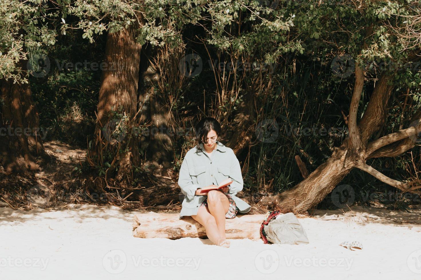 junge marokkanische Frau in der modernen Kleidung, die am Strand sitzt und ein Buch liest foto