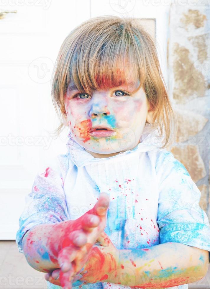 kleines Mädchen schmutzig von Farbe foto