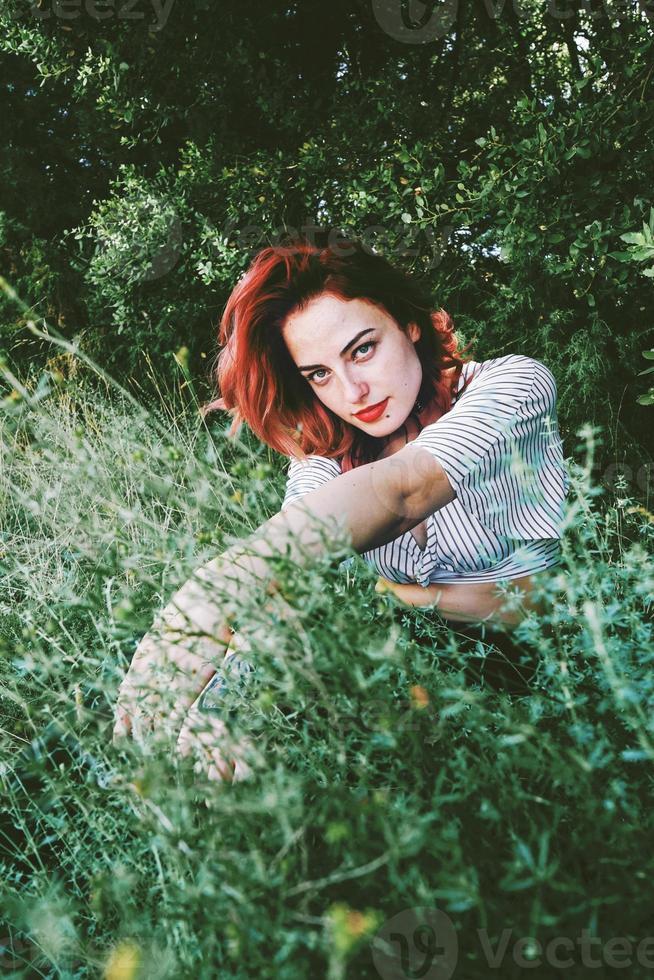 junge und schöne rothaarige Frau posiert umgeben von Natur foto