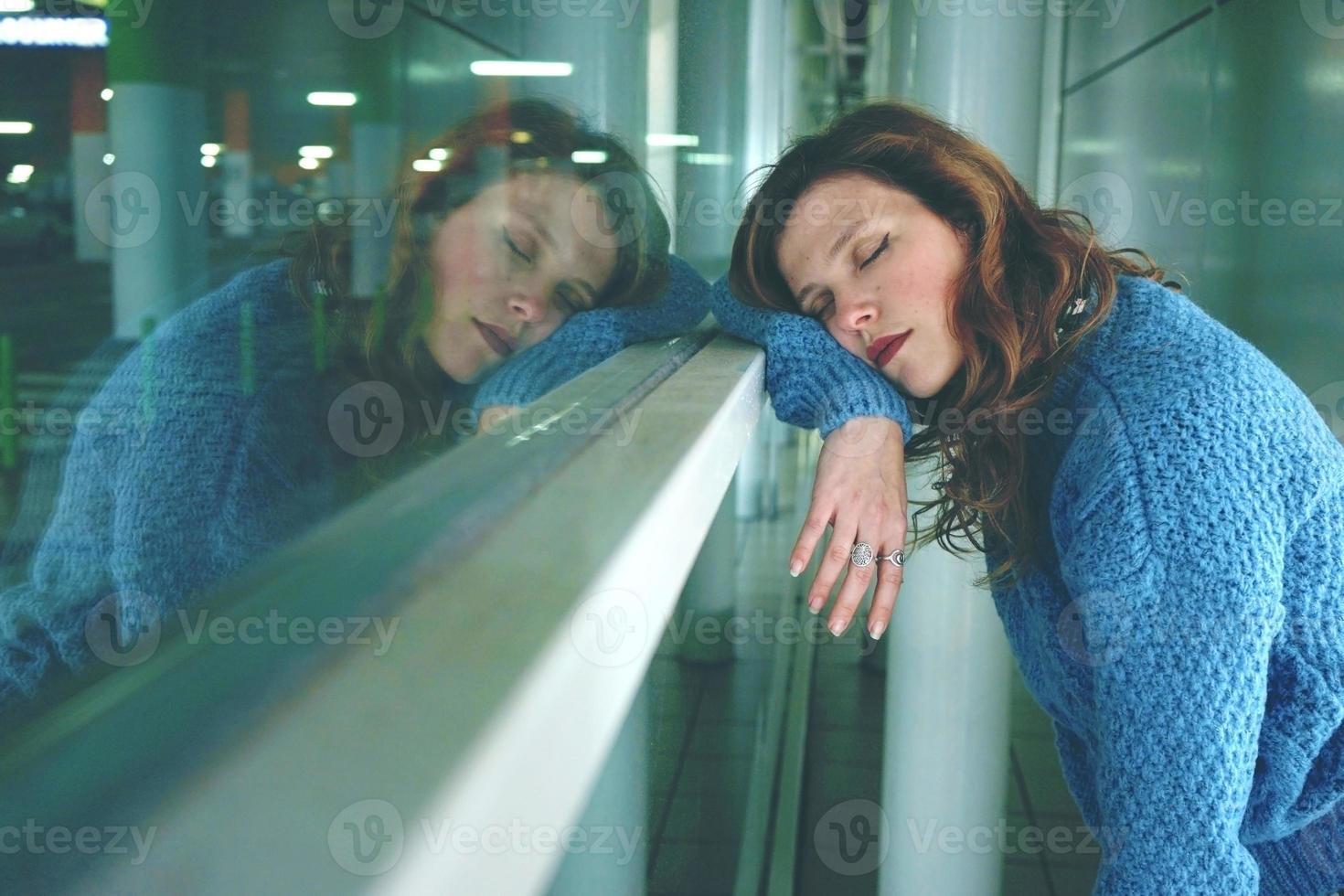 junge Frau allein und müde in einem Busbahnhof foto