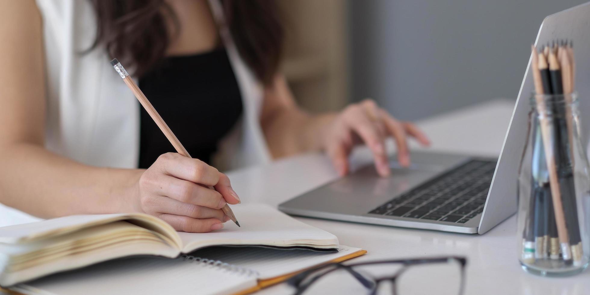 Nahaufnahme einer asiatischen Frau, die auf einem Notebook auf einem Tisch mit Laptop schreibt, Mädchenarbeit in einem Café, freiberufliches Geschäftskonzept foto