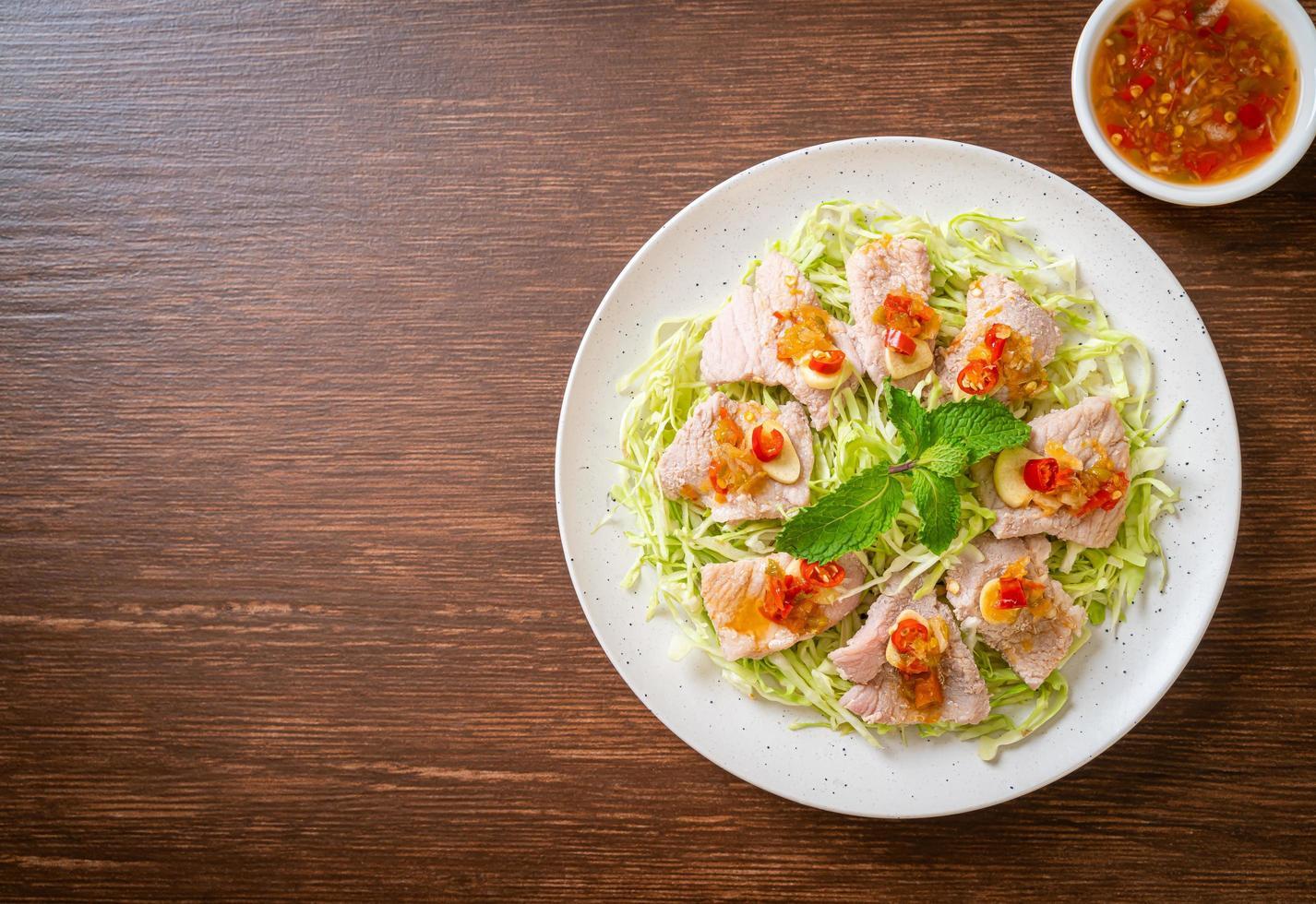 würziger Schweinesalat oder gekochtes Schweinefleisch mit Limetten-Knoblauch und Chilisauce foto