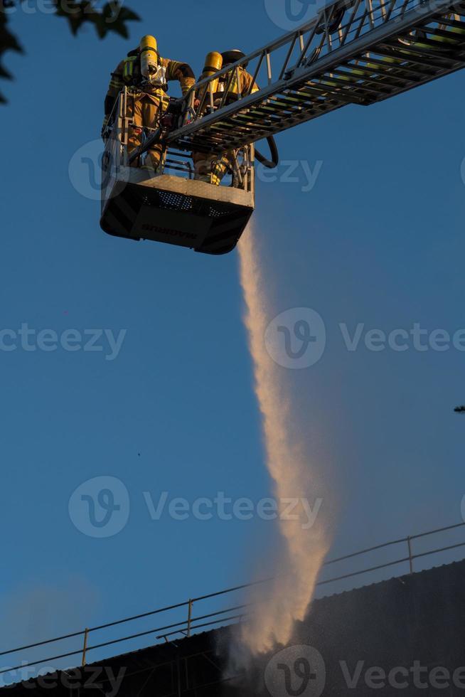 Feuerwehrleute klettern Leiter gegen Bauen und Löschen eines Brandes foto