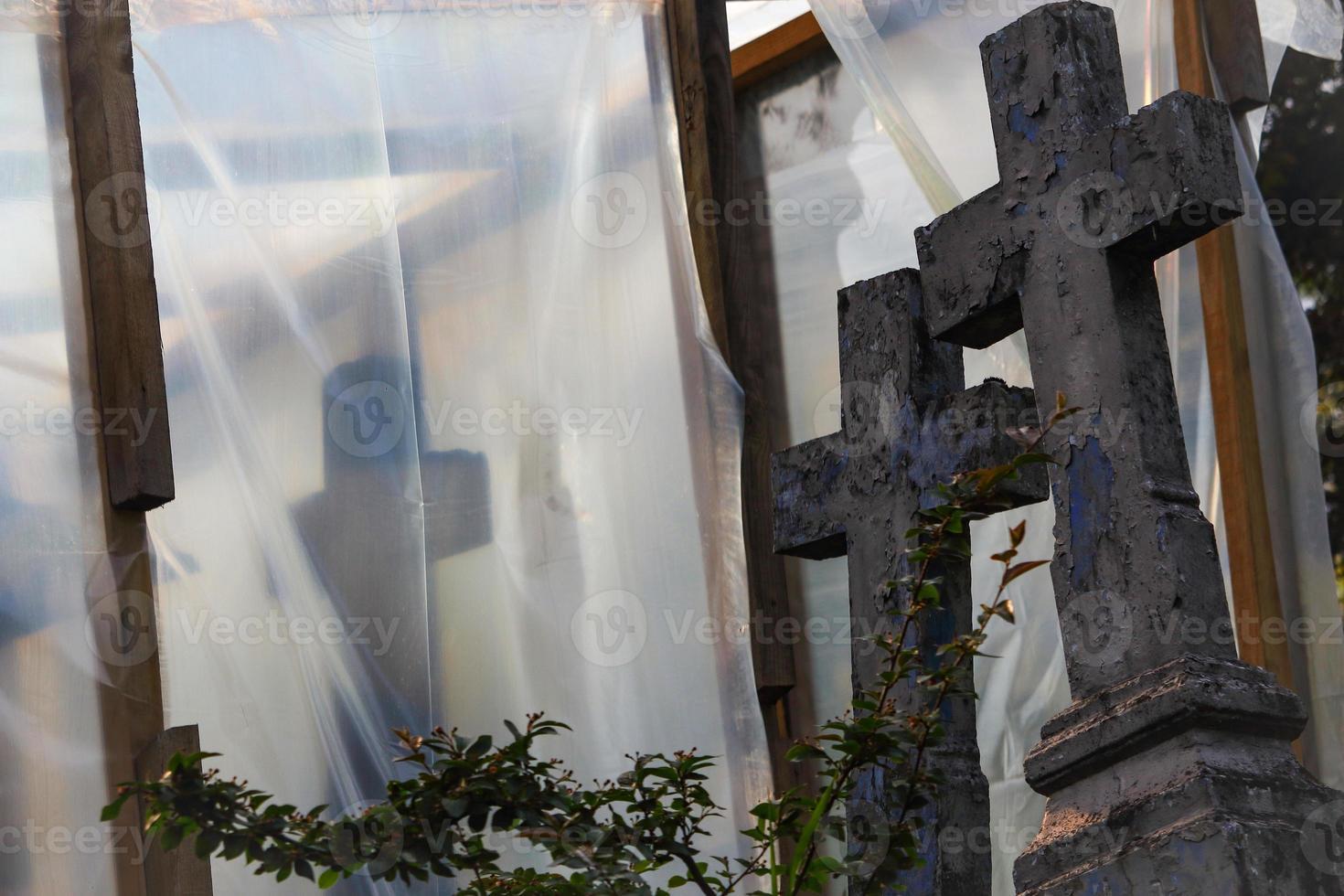 alter Friedhof im Wiederaufbau mit blauem Kreuz hinter einem Busch und mit Plastikfolie auf Holzträgern bedeckt foto
