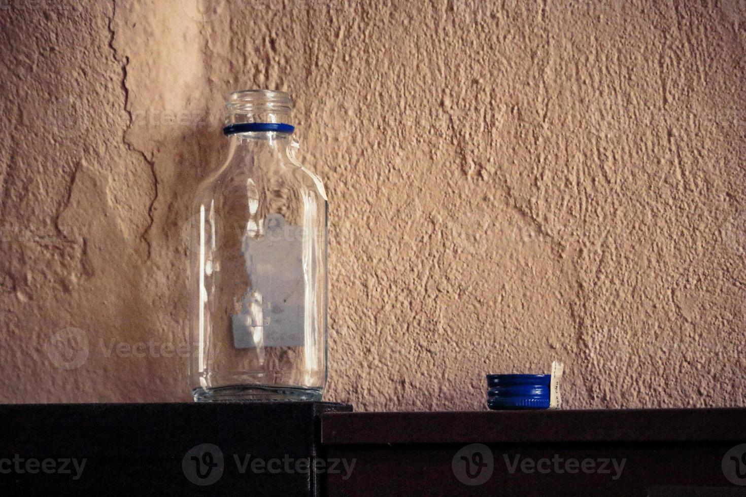 leere kleine Glasflasche mit blauem Metalldeckel auf schwarzem Regal mit Betonhintergrund foto