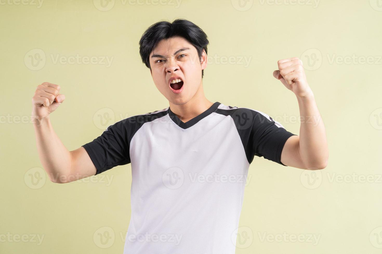 der asiatische mann schrie aus einem triumphierenden ausdruck heraus foto