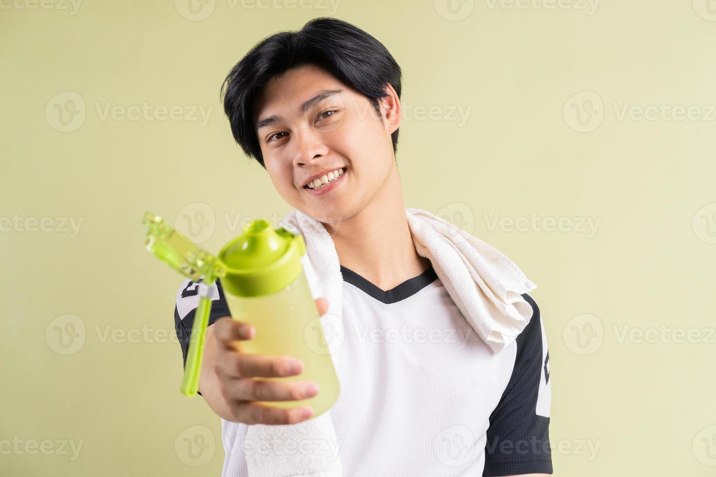 asiatischer Mann mit Wasser in der Hand auf grünem Hintergrund foto