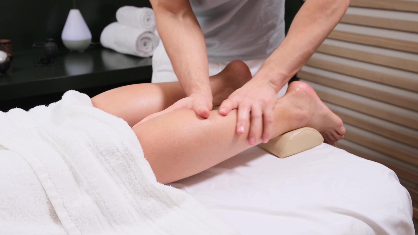 extreme Nahaufnahme eines Osteopathen, der Druck mit dem Daumen auf den weiblichen Wadenmuskel ausübt. foto