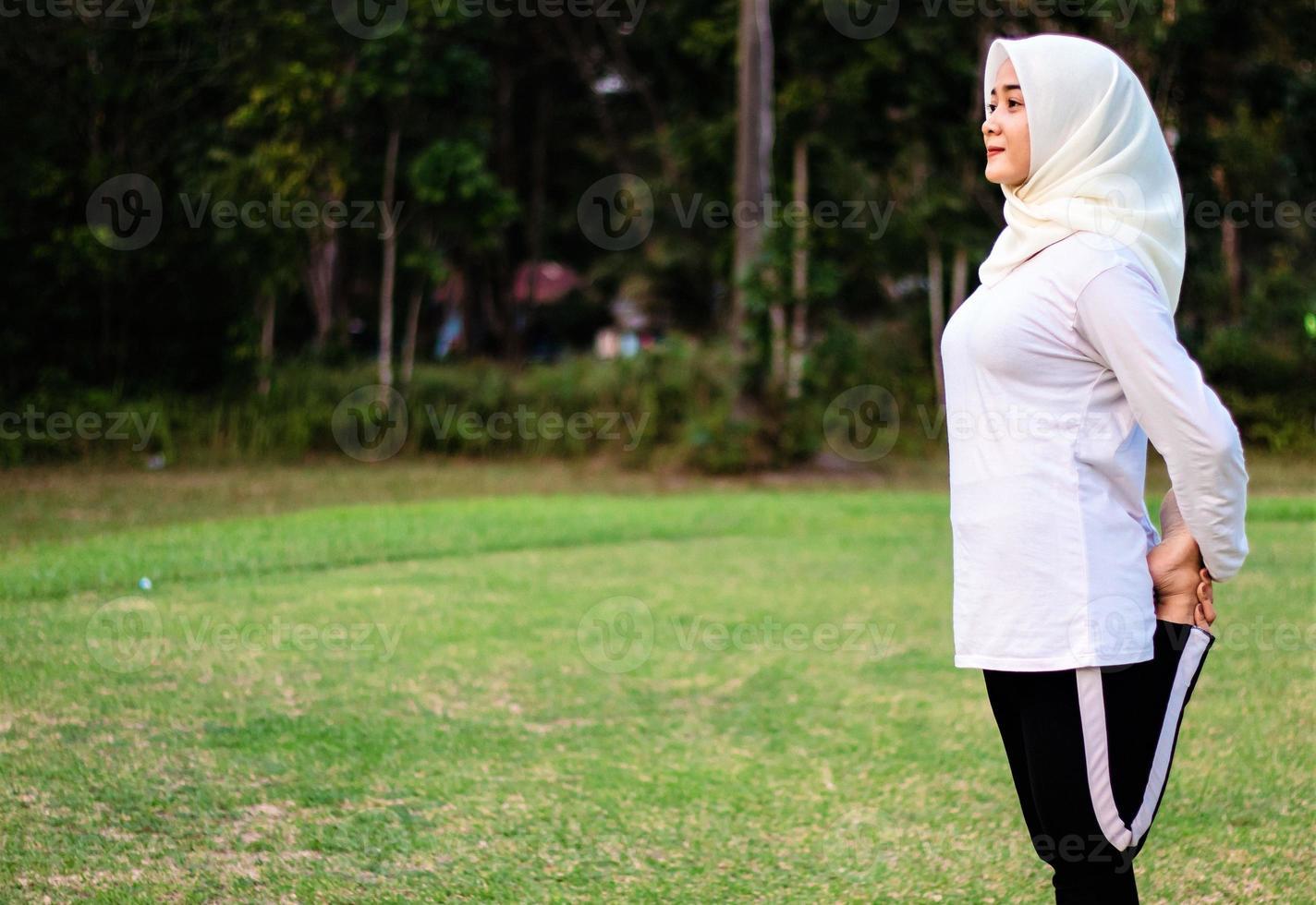 Junge muslimische Frau macht Muskeldehnung, bevor sie Yoga-Bewegungen macht foto