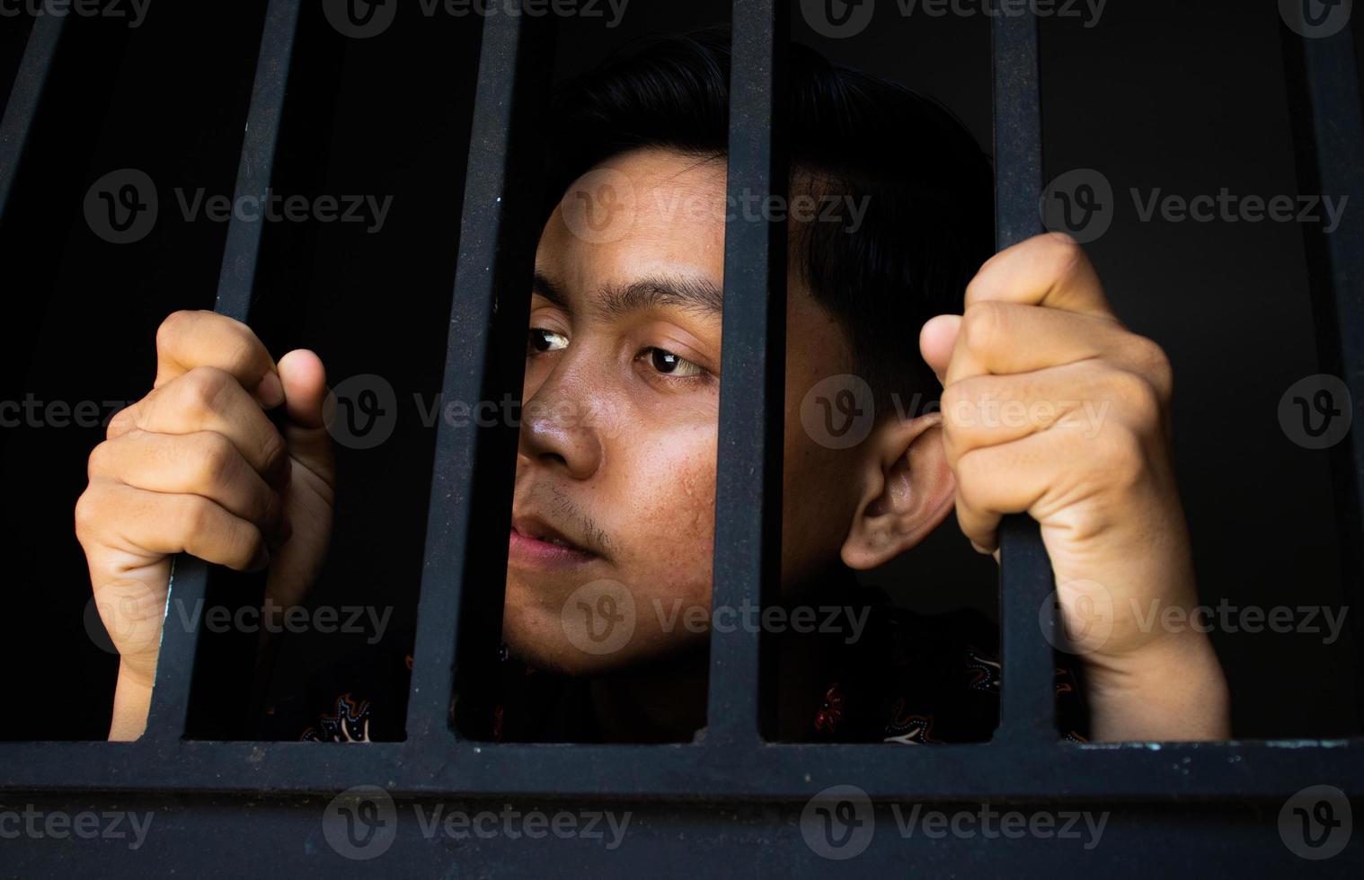 Ausdruck eines Mannes, der im Gefängnis Gitter hält foto