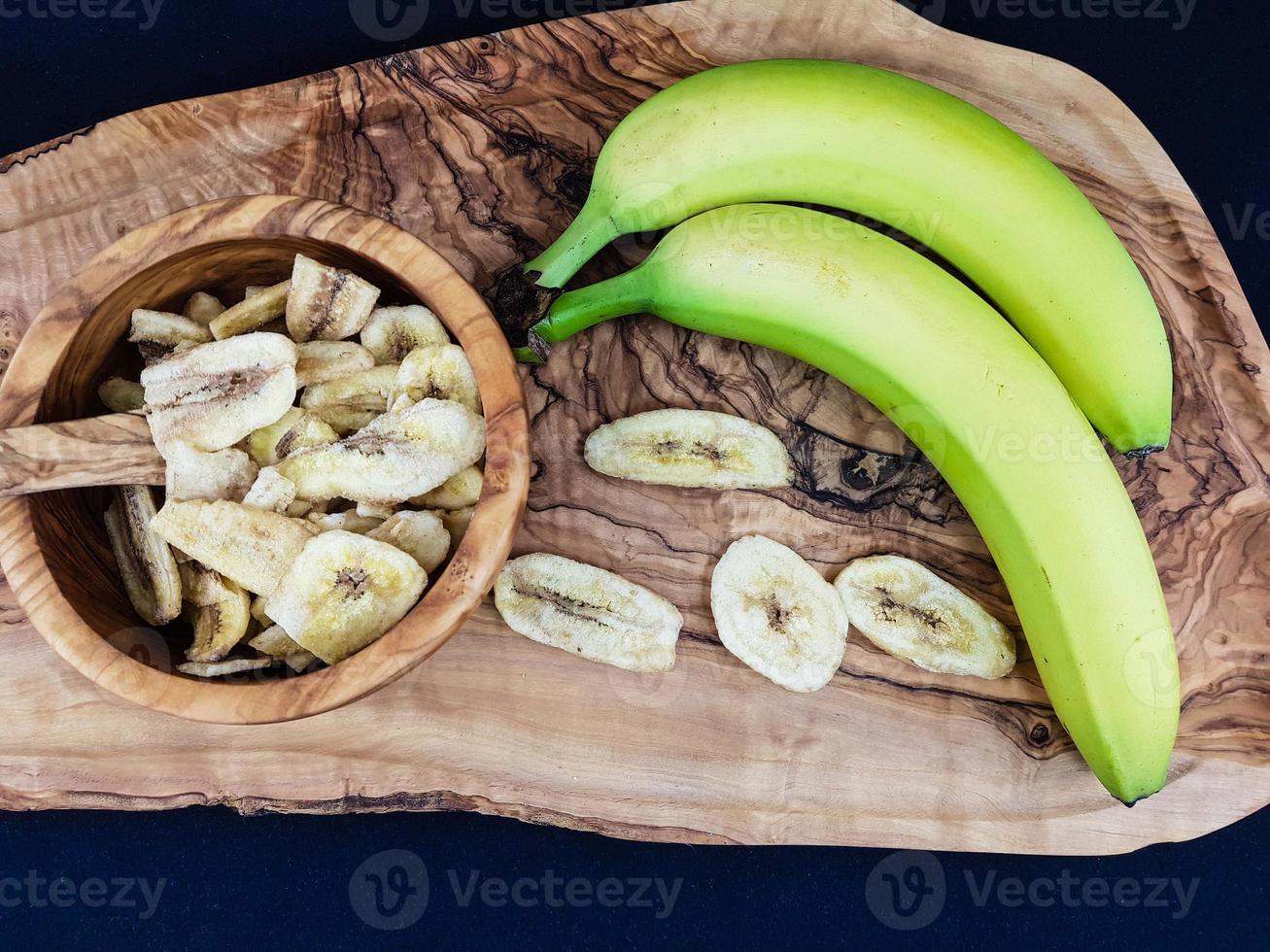 getrocknete Bananenchips auf Olivenholz foto