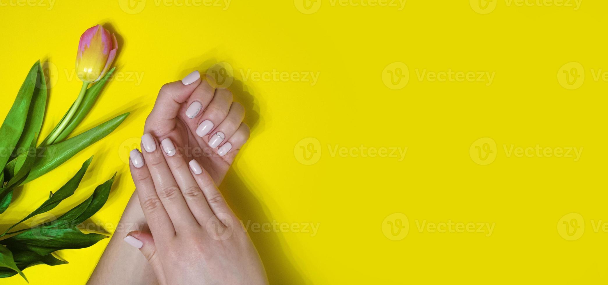 weibliche Maniküre auf hellem Hintergrund. Gelb foto