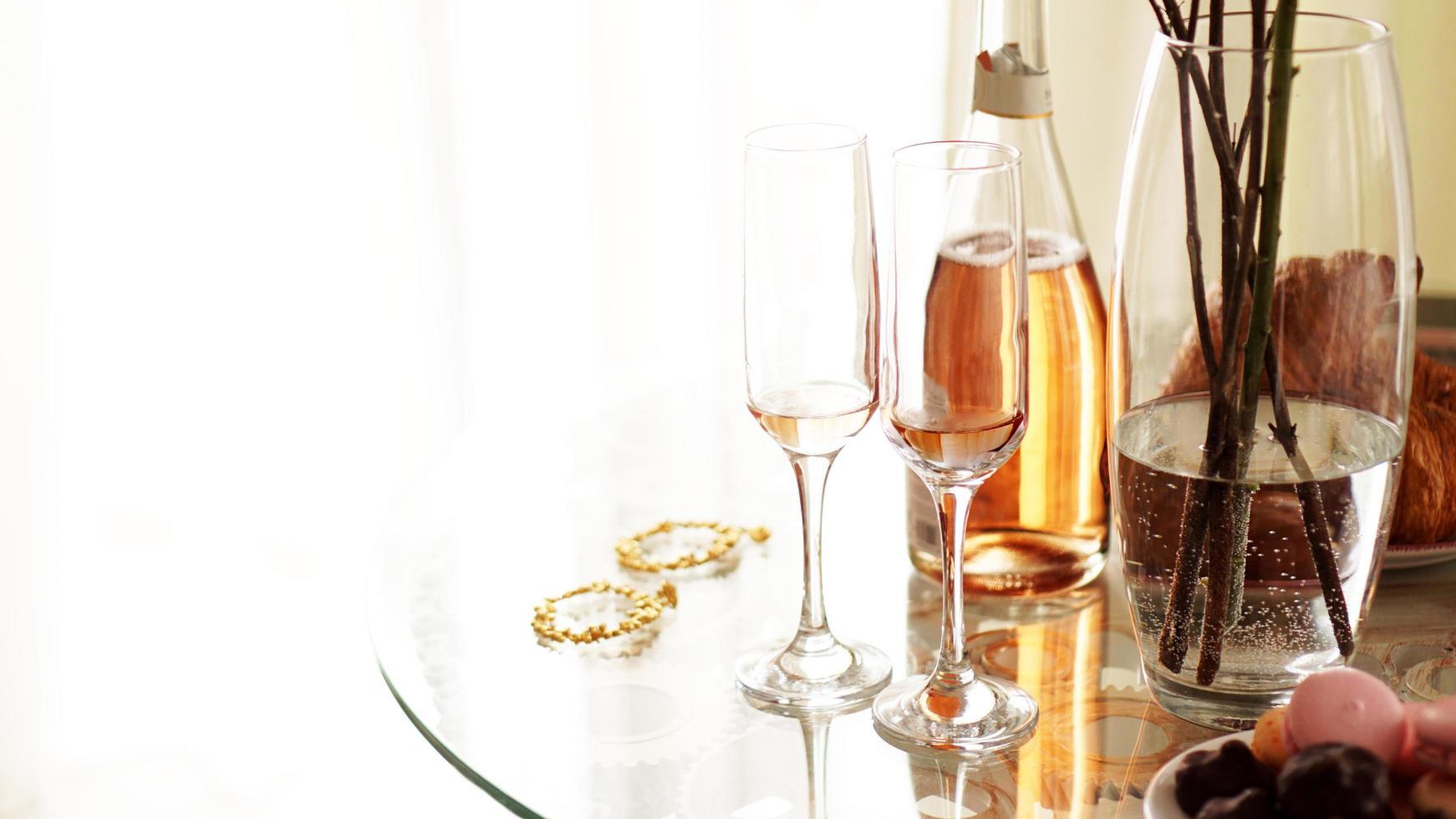 Glastisch auf hellem Hintergrund. zwei Gläser und eine Flasche foto