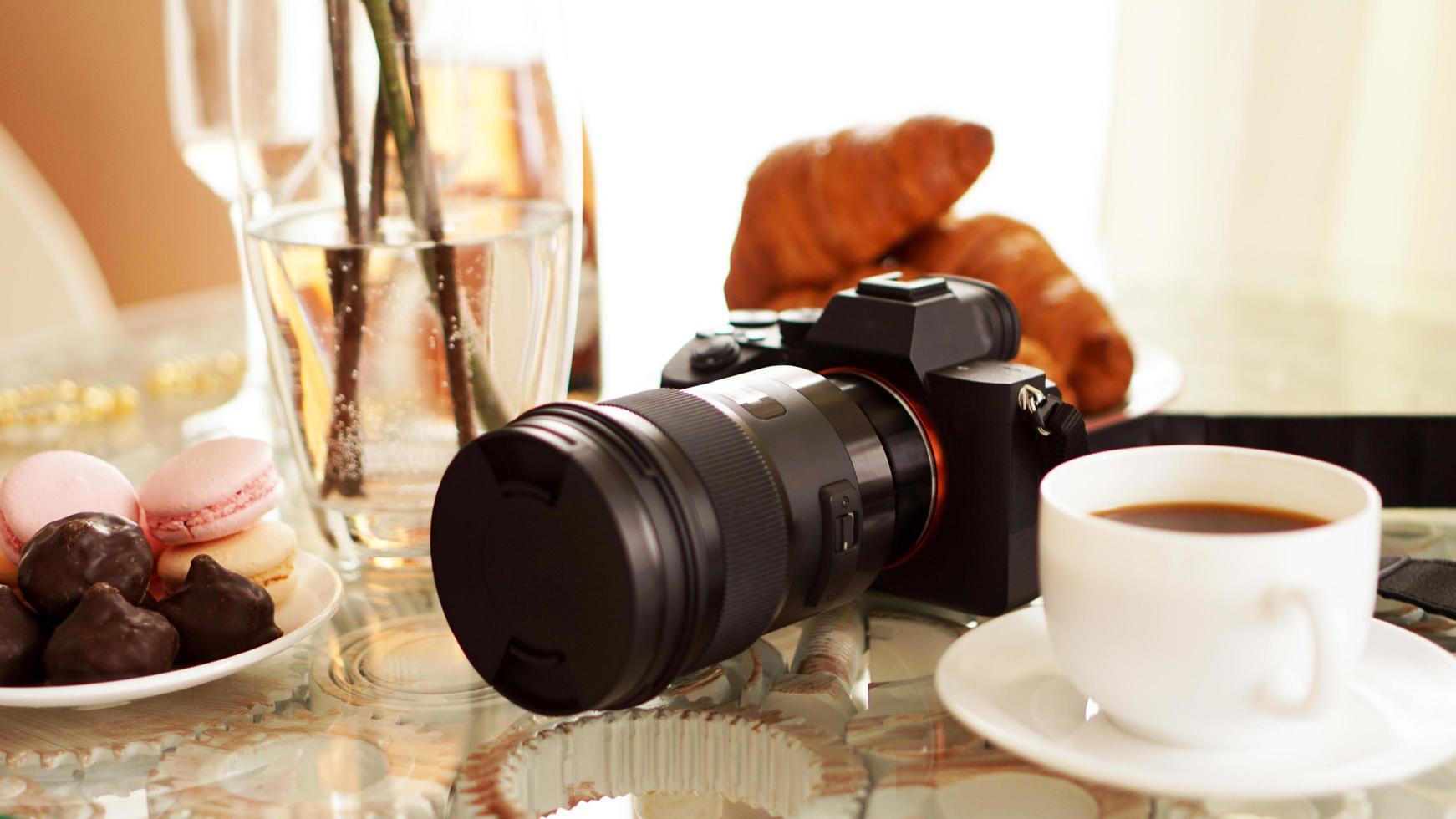Fotokamera mit Objektiv auf Glastisch. Tasse Kaffee foto