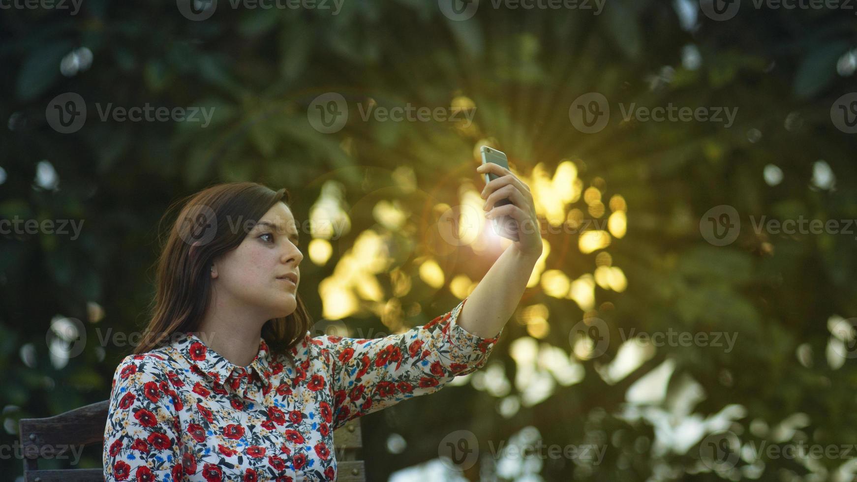 junge Frau in einem Blumenkleid macht ein Selfie foto