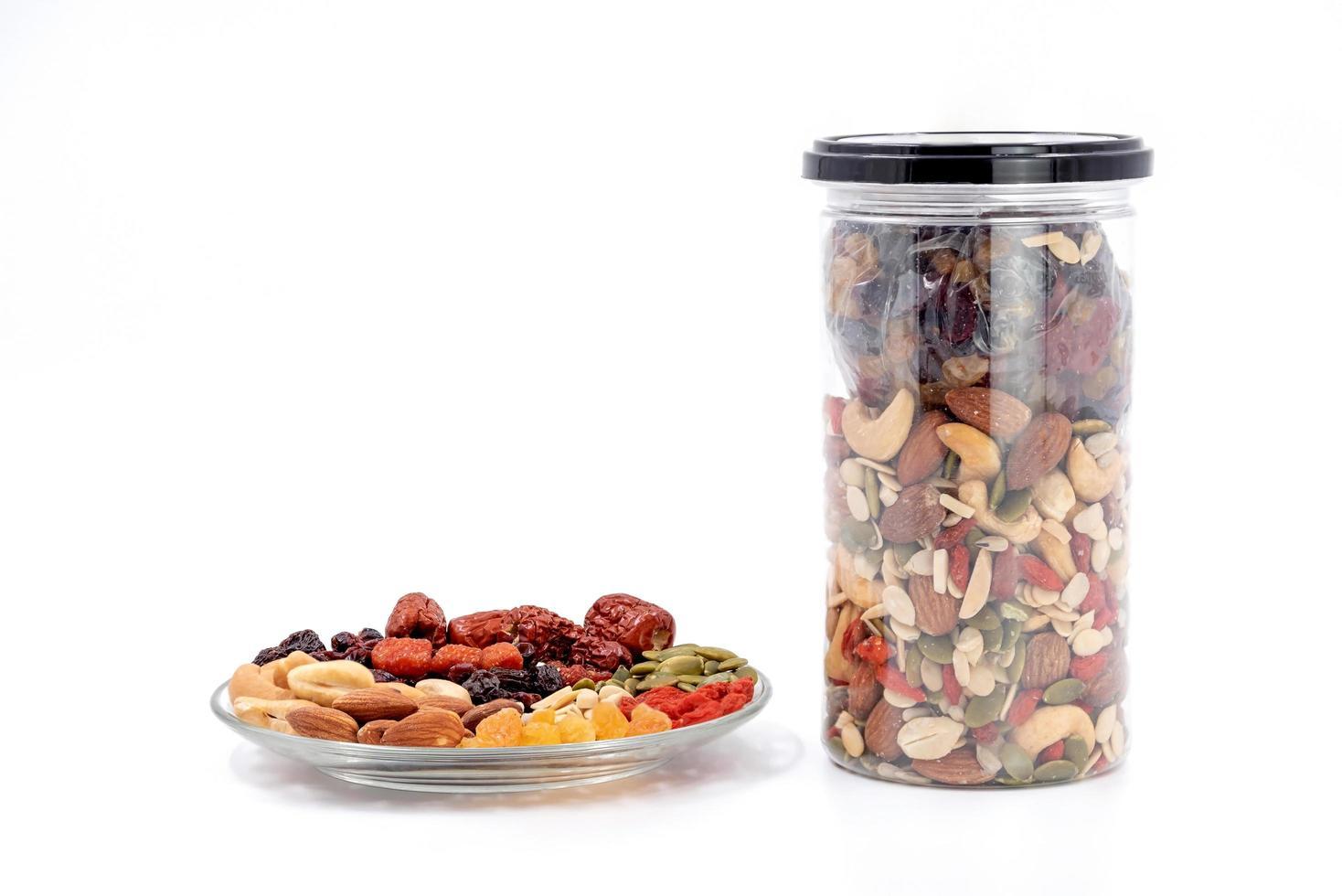 Vollkornprodukte und Trockenfrüchte in einer Glasplatte und einer Plastikflasche. foto
