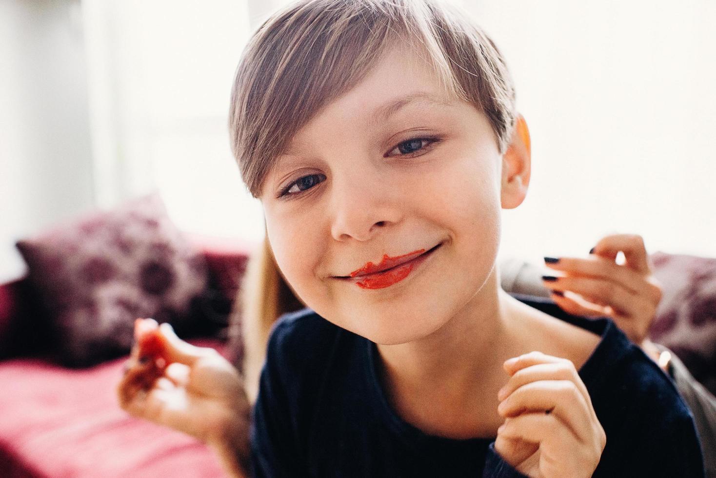 eine weich fokussierte Nahaufnahme eines süßen Jungen mit einem Gesicht, das mit essbarer heller Farbcreme bemalt ist, mit Clownlippen lächelt, ein heller Raum im Hintergrund foto