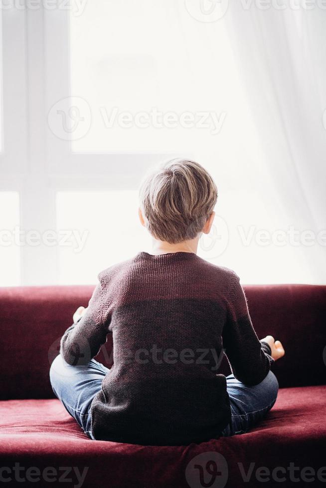 ein Porträt eines Jungen, der in Lotuspose auf einem Sofa sitzt, Blick von seinem Rücken, gegen das helle Fenster, weicher Fokus foto