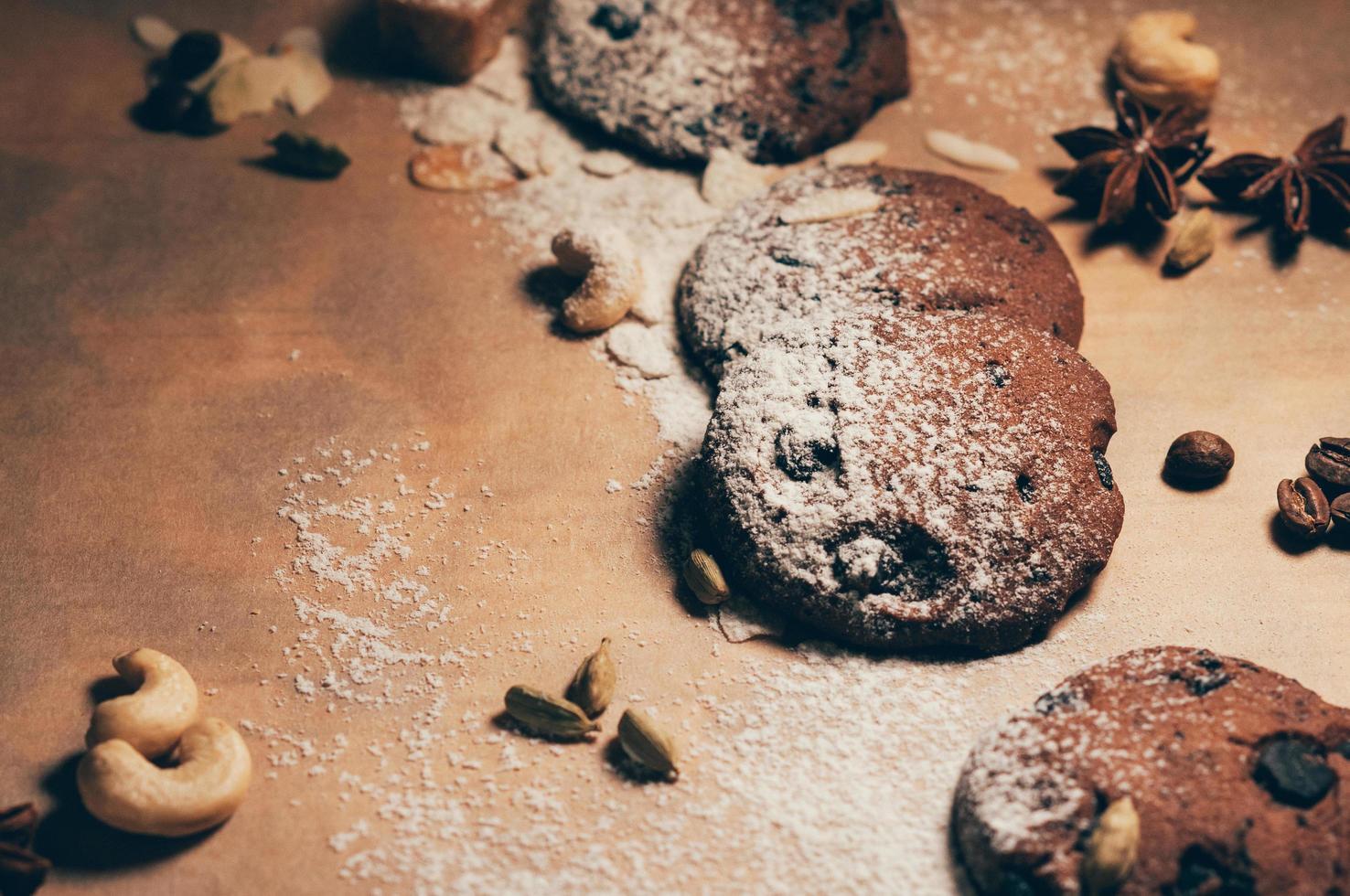 Draufsicht auf knusprige Schokoladenkekse mit Nüssen, Kardamom und Sternanis auf strukturiertem Pergamenthintergrund, bemehlt. Leerer Platz für Ihren Text und Design foto